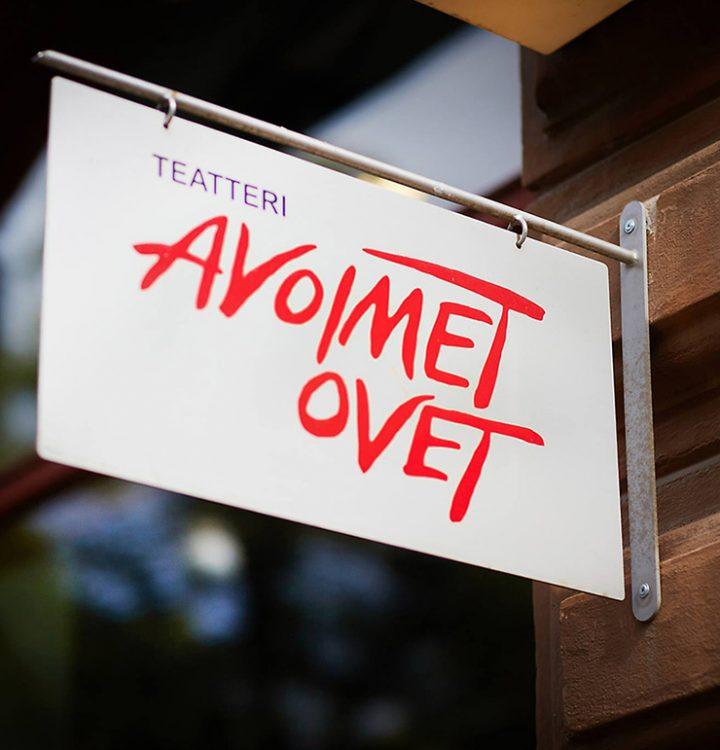 Kuva teatterille vievän porttikongin pielessä olevasta kylstistä, jossa Teatteri Avoimien Ovien logo punaisella valkoisella pohjalla