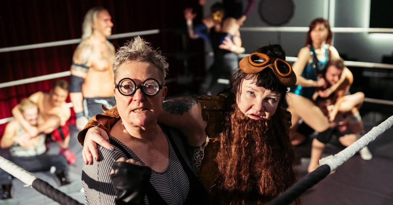 Kuvassa Tiina Weckström ja Minna Kivelä rooleissaan showpainikehässä. Taustalla showpainijoita.