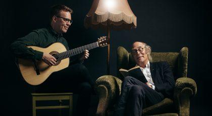 Kuvassa Petri Kumela kitaran kanssa ja hänen vieressään istuu vesa Vierikko nojatuolissa lukien kirjaa
